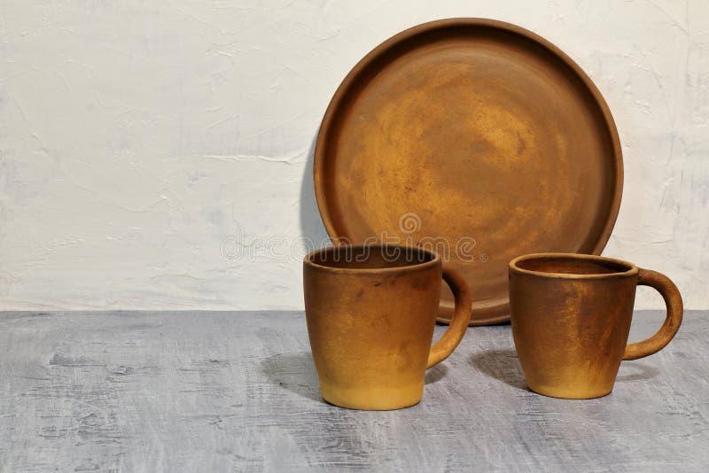 Круглый поднос глины около белых кофейных чашек бетонной стены и глины на темной конкретной столешнице стоковое фото rf