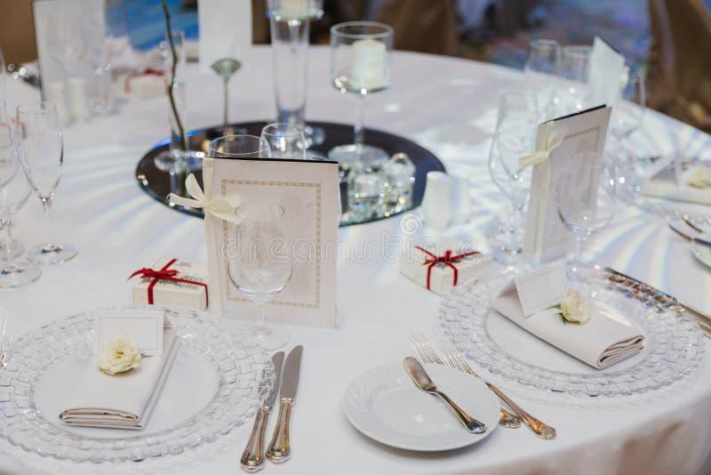 Круглый стол, который служат с пустыми плитами, ножами, вилками, картой и салфетками, предусматриванными с белыми tableclothes Ст стоковое изображение
