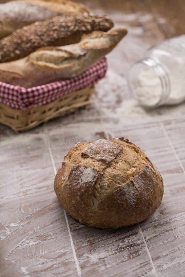 Круглый хлеб с корзиной различного хлеба формирует на деревянном столе стоковые фотографии rf