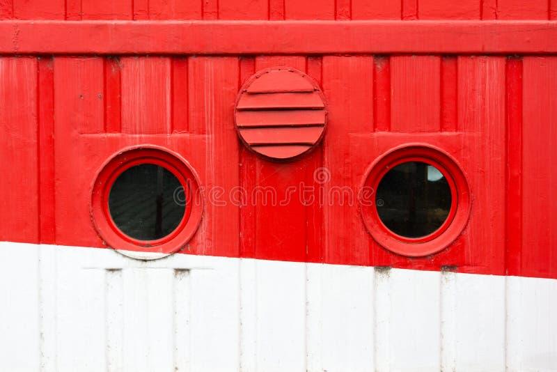 Круговые окна на красном и белом туристическом судне стоковые фотографии rf