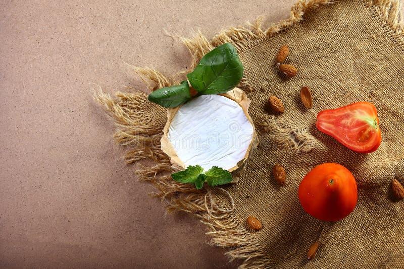 Круг сыра камамбера или бри в коричневой бумаге kraft украшенной с базиликом и частями томатов, на старой клочковатой ткани, взгл стоковое изображение