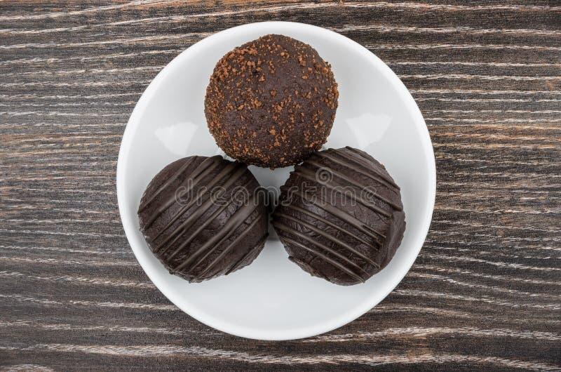 Круглый шоколадный торт 3 в стеклянном поддоннике на темной таблице стоковое фото rf