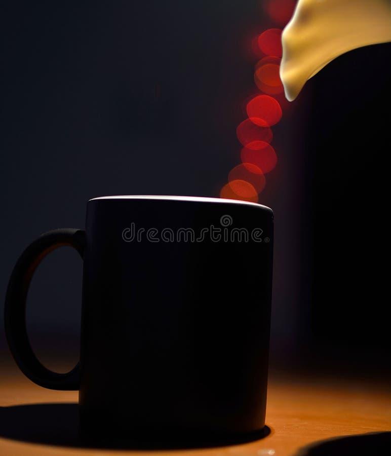 Кружка кофе будучи заполнянной bokeh освещает стоковые изображения
