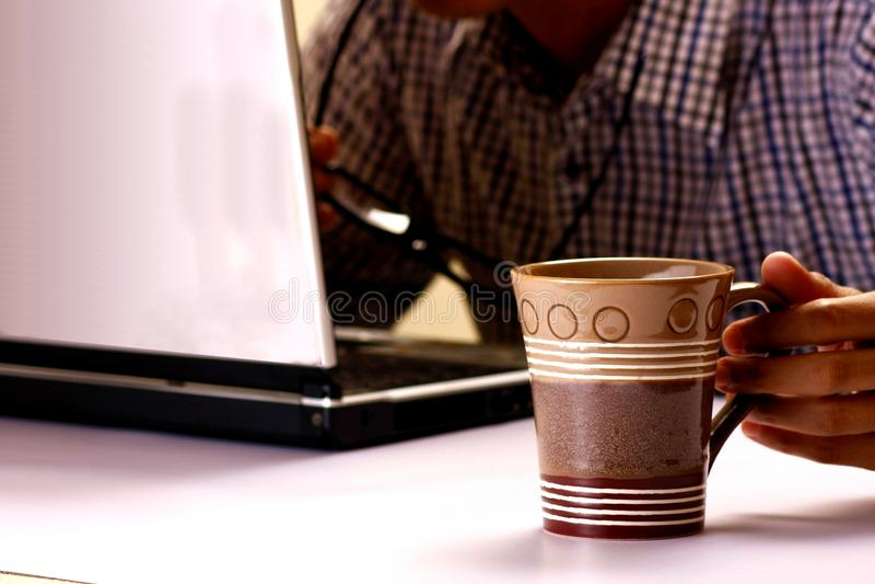 Кружка кофе держала человеком работая на портативном компьютере на заднем плане стоковая фотография rf