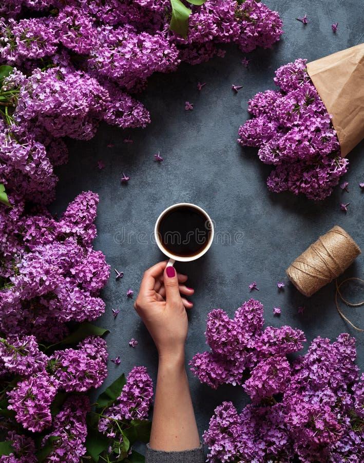 Кружка кофе с букетом сирени весны цветков разветвляет blossoming в месяце мая на сером взгляде предпосылки от стоковое фото