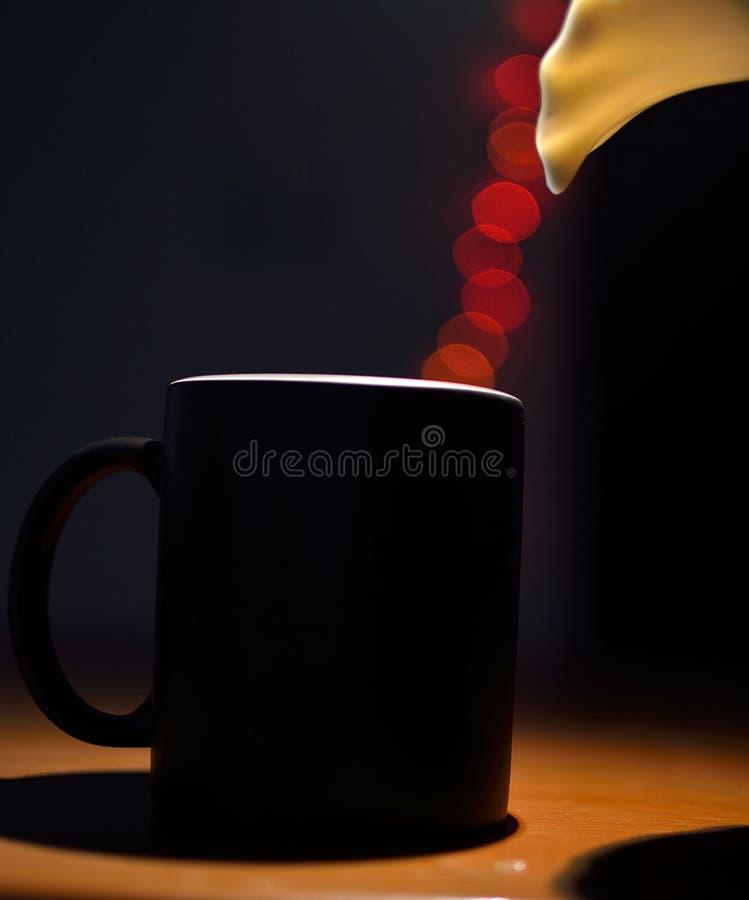 Кружка кофе с красными светами bokeh стоковое изображение