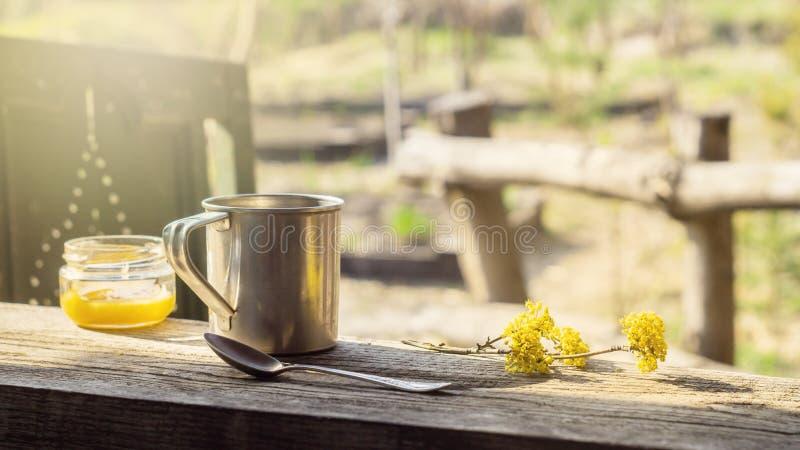 Кружка металла, опарник меда и цветя ветвь на деревянном столе стоковые изображения