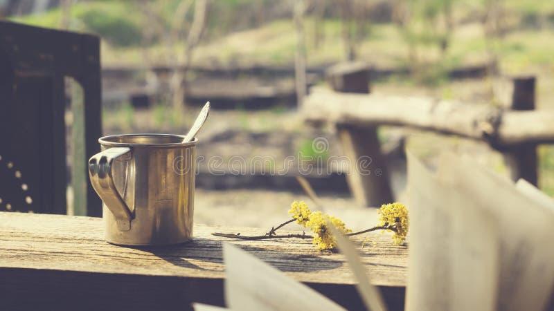 Кружка металла, цветя ветвь и книга на деревянном столе стоковая фотография rf