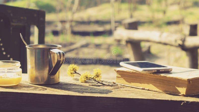 Кружка металла, цветя ветвь и телефон на деревянном столе стоковое фото