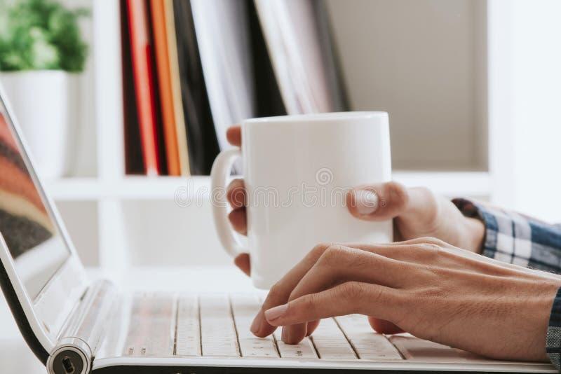 Кружка чая в руке над компьтер-книжкой стоковые изображения rf