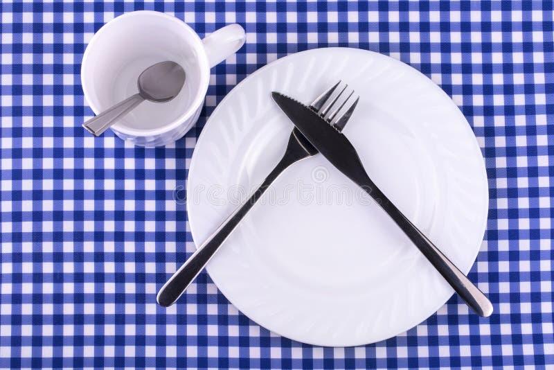 Кружка Empy с ложкой, плитой с ножом и вилкой стоковая фотография
