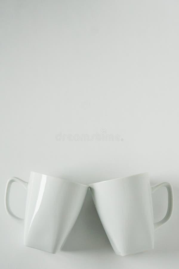 Кружки белого кофе на белой предпосылке clinking в приветственных восклицаниях с пустым космосом экземпляра стоковые изображения
