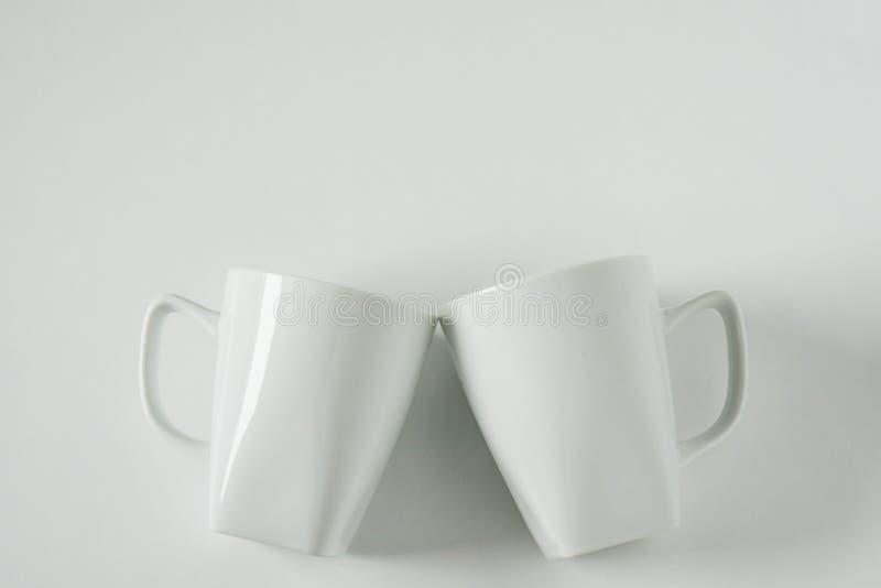 Кружки белого кофе на белой предпосылке clinking в приветственных восклицаниях с пустым космосом экземпляра стоковое фото rf