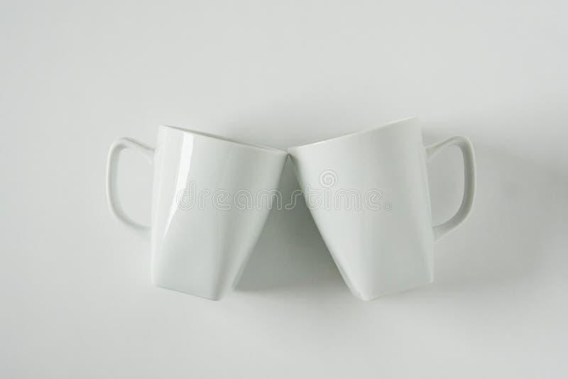 Кружки белого кофе на белой предпосылке clinking в приветственных восклицаниях с пустым космосом экземпляра стоковое фото