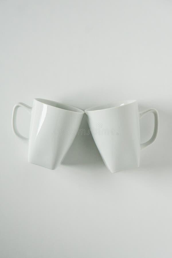 Кружки белого кофе на белой предпосылке clinking в приветственных восклицаниях с пустым космосом экземпляра стоковое изображение