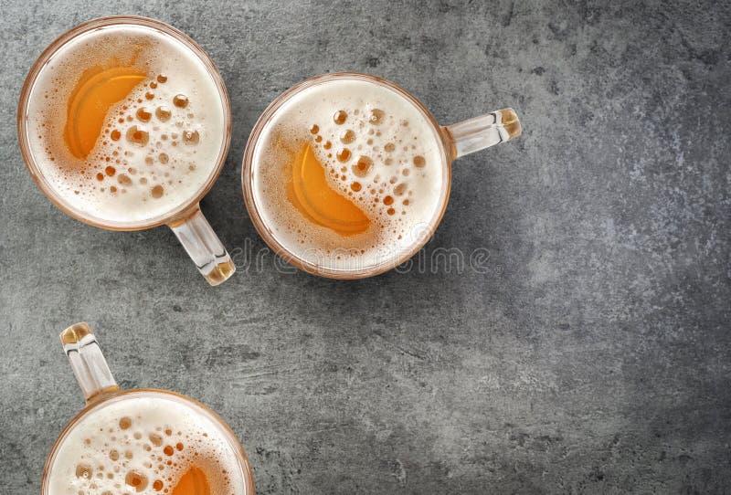 Кружки пива на серой таблице стоковое фото