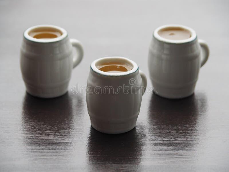 Кружки пива на темном деревянном столе стоковые фото