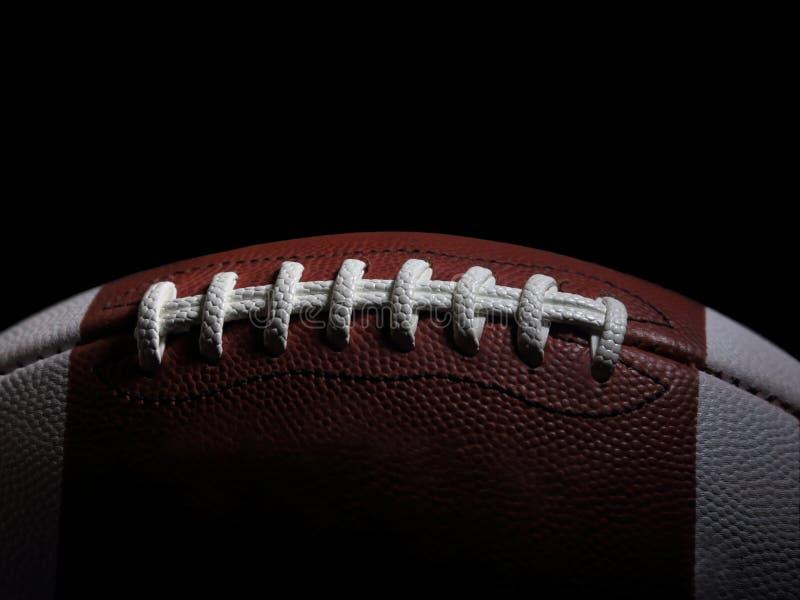 Крупный план американского шарика футбольной игры против черного Backgr стоковое фото