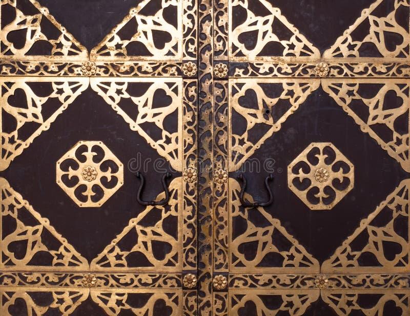 Крупный план античной двери церков с золотое богато украшенным стоковая фотография