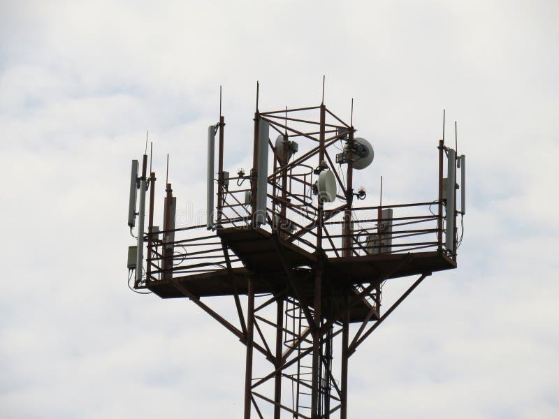 Крупный план башни мобильного телефона связи на предпосылке облачного неба стоковое изображение
