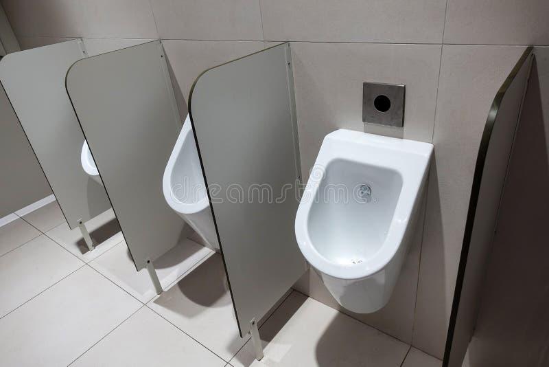 Крупный план 3 белых писсуаров в дизайне ванной комнаты ` s людей белых керамических писсуаров для людей в комнате туалета, стене стоковые фотографии rf
