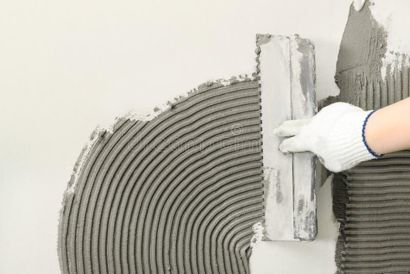 Крупный план бетона работника распространяя на стене со шпателем Кафельная установка стоковая фотография