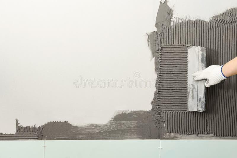 Крупный план бетона работника распространяя на стене со шпателем Кафельная установка стоковые изображения