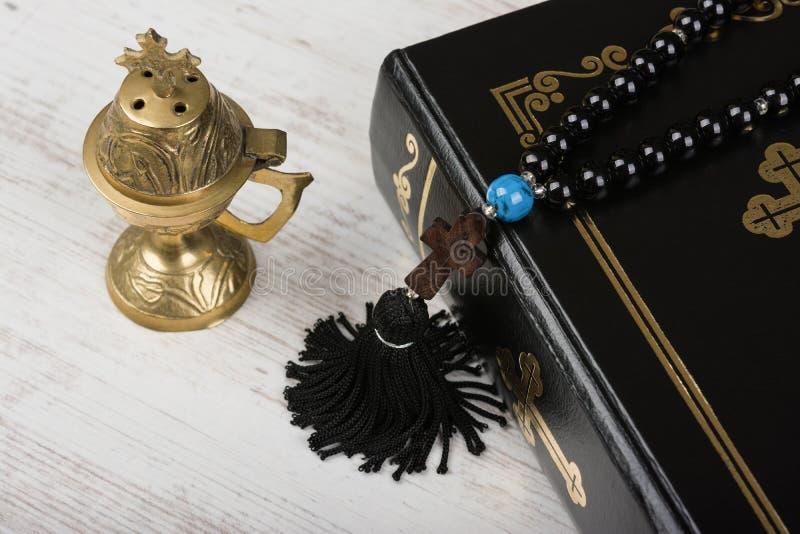 Крупный план библии, шарики розария с крестом и горелка ладана на белой деревянной предпосылке Концепция и вера вероисповедания стоковые фотографии rf