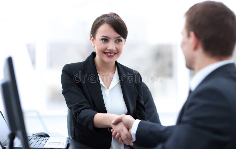 Крупный план бизнес-леди тряся руки с ее коллегой стоковое изображение