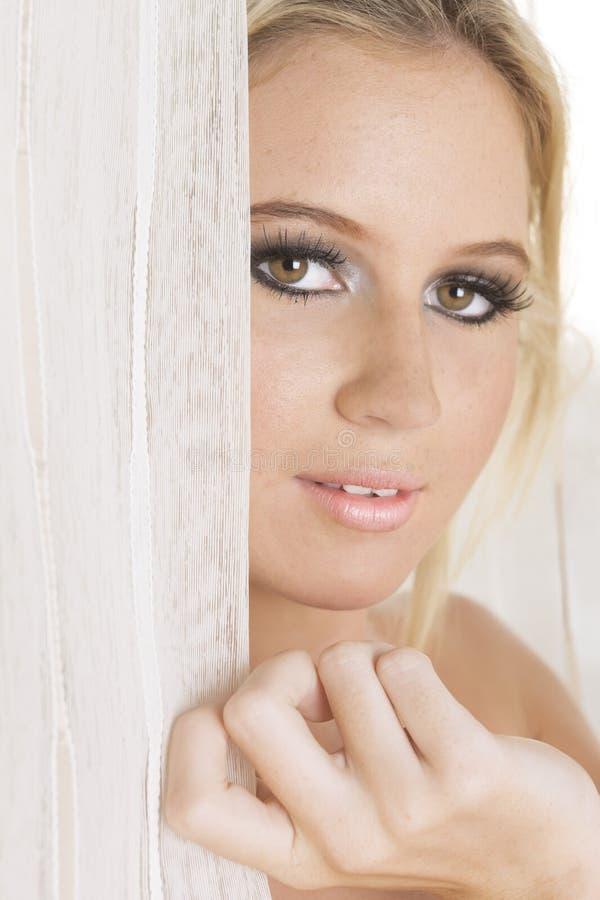 Крупный план блондинкы между занавесами показывая ее сторону стоковое фото