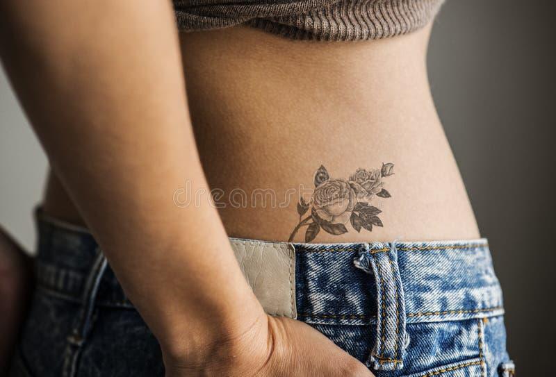 Крупный план более низкой тазобедренной татуировки женщины стоковые фотографии rf