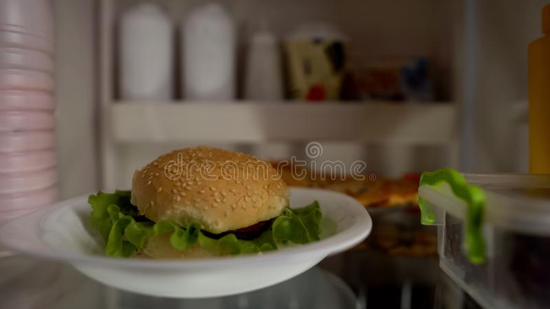 Крупный план бургера в холодильнике, концепции высококалорийной вредной пищи, нездоровом питании, калориях стоковое изображение rf