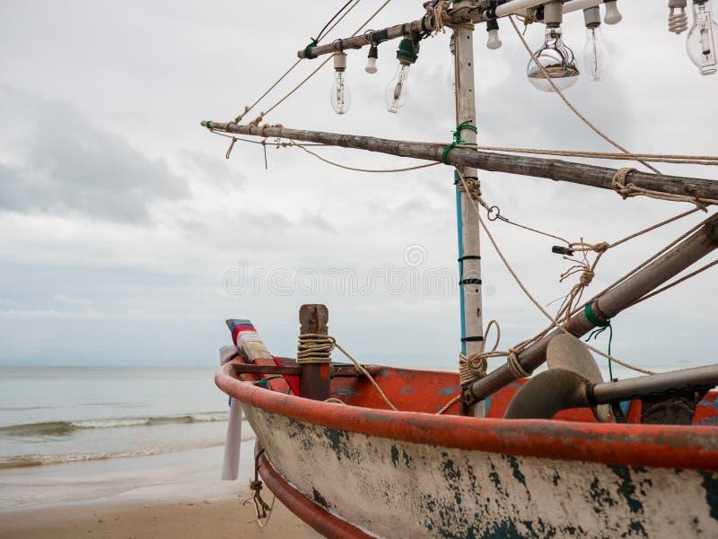 Крупный план головы шлюпки рыбацкой лодки и электрической лампочки кальмара на пляже в пасмурном дне утра стоковая фотография