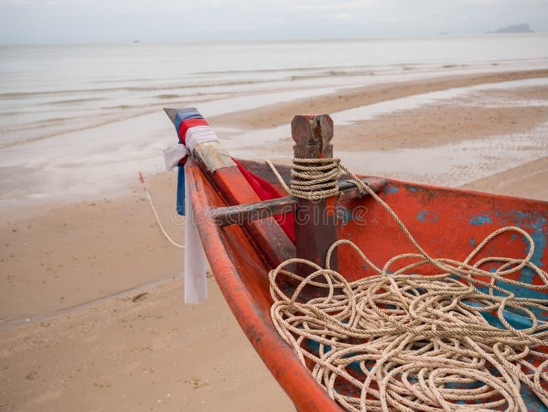 Крупный план головы шлюпки рыбацкой лодки кальмара с веревочкой на пляже в пасмурном дне утра стоковая фотография rf