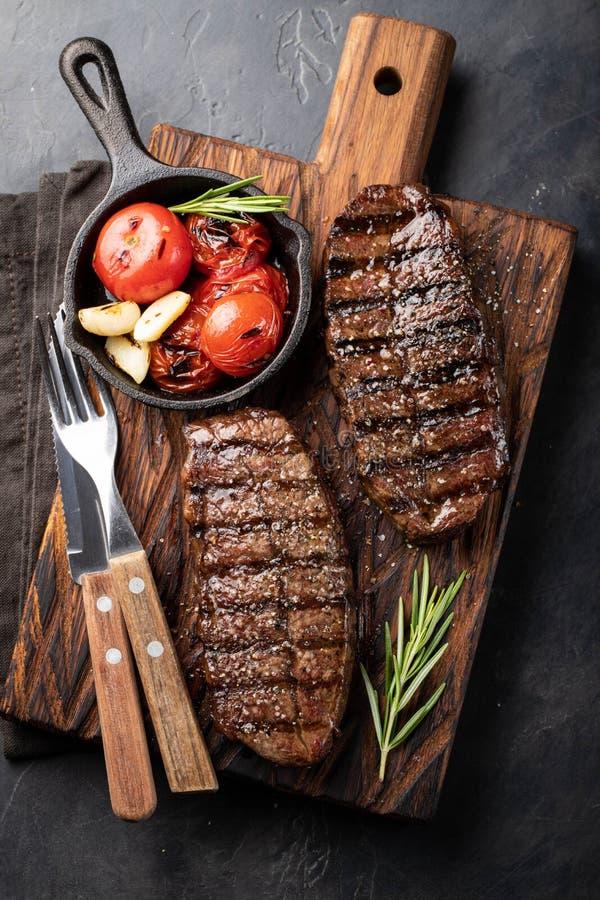 Крупный план готовый для еды пород говядины лезвия стейка верхних черного Ангуса с томатом гриля, чесноком и на деревянной доске  стоковые изображения