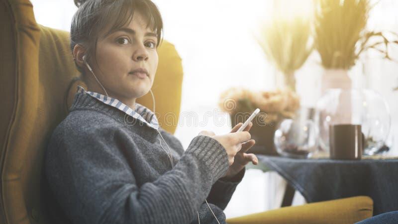 Крупный план девушка в наушниках держа телефон сидя в большом стуле стоковые изображения