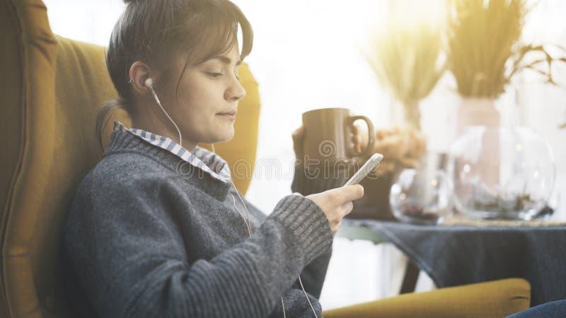 Крупный план девушка в наушниках держа телефон сидя в чае большого стула выпивая стоковое изображение