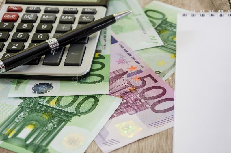 крупный план евро 500, ручка, часть банкнот блокнота, калькулятора и евро стоковое изображение