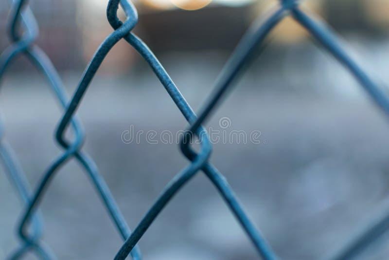 Крупный план загородки сетки металла, с запачканной вне предпосылкой bokeh стоковые изображения