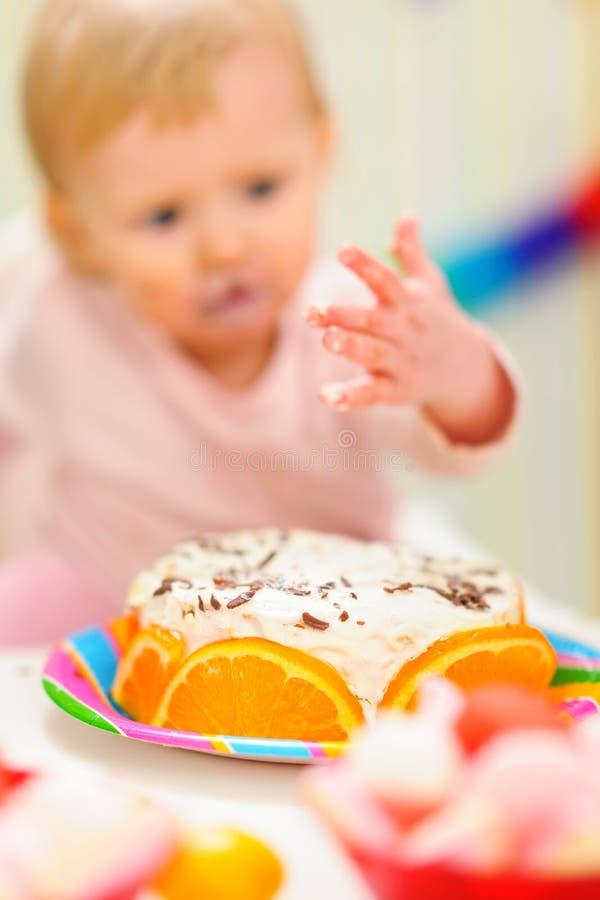 крупный план именниного пирога младенца ест смазано стоковое изображение