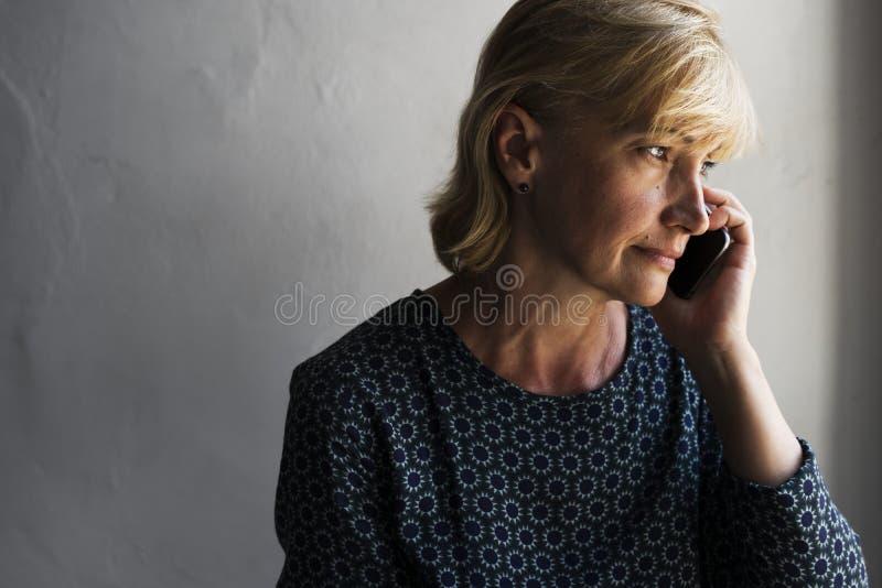 Крупный план кавказской женщины вызывая мобильный телефон с заботливым выражением стороны стоковое фото