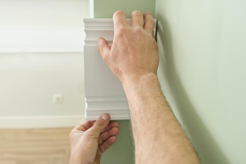Крупный план клеить деревянную белую покрашенную панель планки на стене, крупном плане, плотничестве, работе по дереву, профессии стоковое изображение