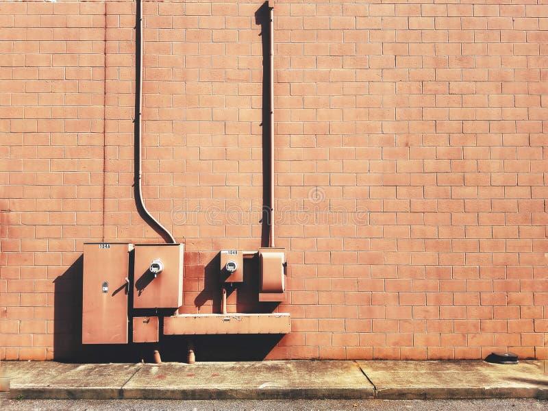Крупный план коробок электрического взрывателя на коричневой кирпичной стене стоковое фото