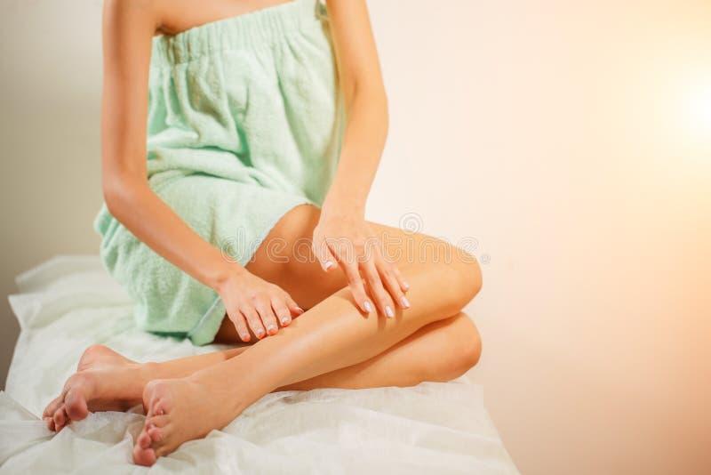 Крупный план красивой руки ` s женщины с ногами естественного маникюра касающими сексуальными длинными стоковое изображение rf