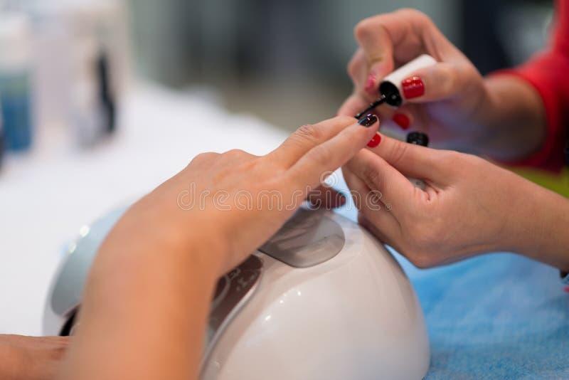 Крупный план красивых рук женщины получая маникюр в салоне спа стоковое изображение rf