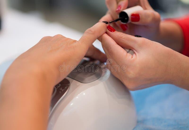Крупный план красивых рук женщины получая маникюр в салоне спа стоковые фотографии rf