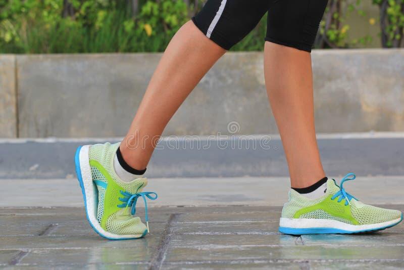 Крупный план на ботинке, женщине бежать на утре в парке, фитнесе и здоровой концепции образа жизни стоковые изображения