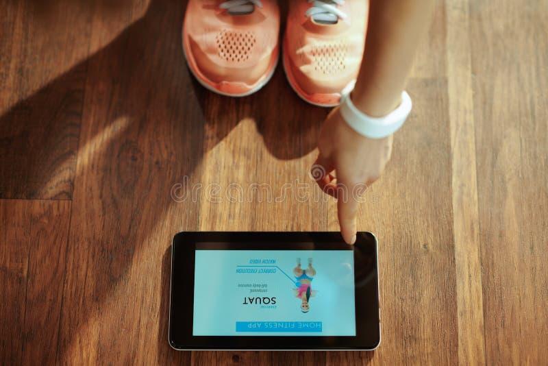 Крупный план на женщине используя домашнее приложение тренера в ПК планшета стоковое изображение