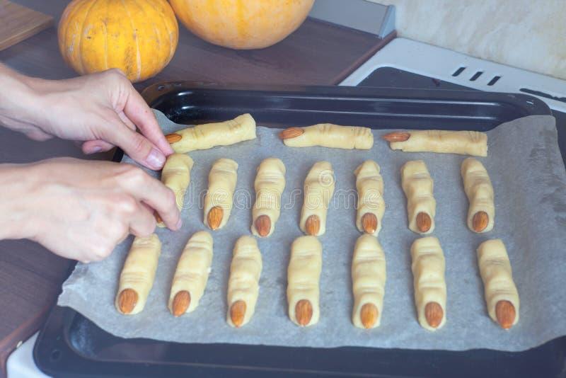Крупный план на подносе с сырыми печеньями хеллоуина на таблице в кухне Хеллоуин обрабатывает готовое для того чтобы пойти в печь стоковая фотография