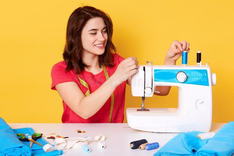 Крупный план на привлекательной белошвейке кладя иглу в швейную машину, имеет счастливое выражение лица, нося красную случайную ф стоковое изображение rf